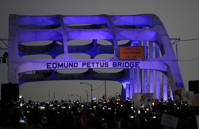"""Marchers hold up a their cellular phones to record the rapper Common and singer song writer, John Legend preform at the foot of the Edmund Pettus Bridge in honor of Martin Luther King Jr., Sunday, Jan. 18, 2015, in Selma, Ala. Several celebrities such as Oprah Winfrey, John Legend, Common, and David Oyelowo lock arms and march to promote the movie """"Selma.""""(AP Photo/Brynn Anderson)"""