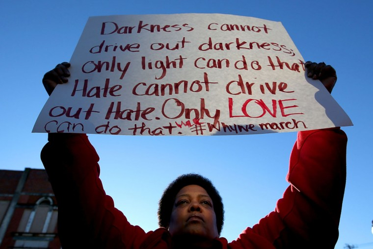 """Barbara Carter holds up a sign as thousands marched across the Edmund Pettus Bridge along with members of the cast of the movie """"Selma"""" in honor of Rev. Martin Luther King Jr. Day on January 18, 2015 in Selma, Alabama. In 1965, King led thousands of nonviolent protestors on a march through Selma to the state capitol in a historic Civil Rights demonstration. (Photo by Sean Gardner/Getty Images)"""
