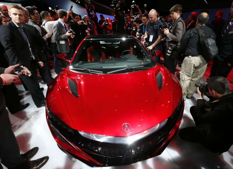 Media surround the Acura NSX at its debut during media previews for the North American International Auto Show in Detroit Monday, Jan. 12, 2015. (AP Photo/Paul Sancya)