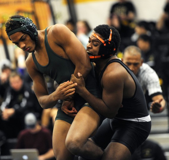Wilde Lake's Ernie Fermin, left, tries to escape the grip of Oakland Mills' Sidique Furet during a wrestling tri-meet between Oakland Mills, Wilde Lake and Mt. Hebron at Mt. Hebron High School in Ellicott City, Thursday, Jan. 8, 2015. (Jon Sham/BSMG)
