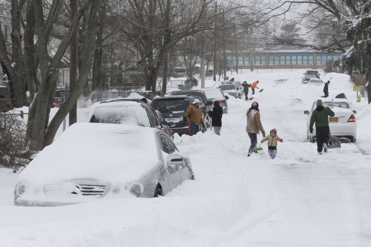 Residents of Central Islip, N.Y. clear snow from their street, Tuesday, Jan. 27, 2015. A storm packing blizzard conditions spun up the East Coast early Tuesday, pounding coastal eastern Long Island into Maine with high winds and heavy snow. (AP Photo/Mary Altaffer)