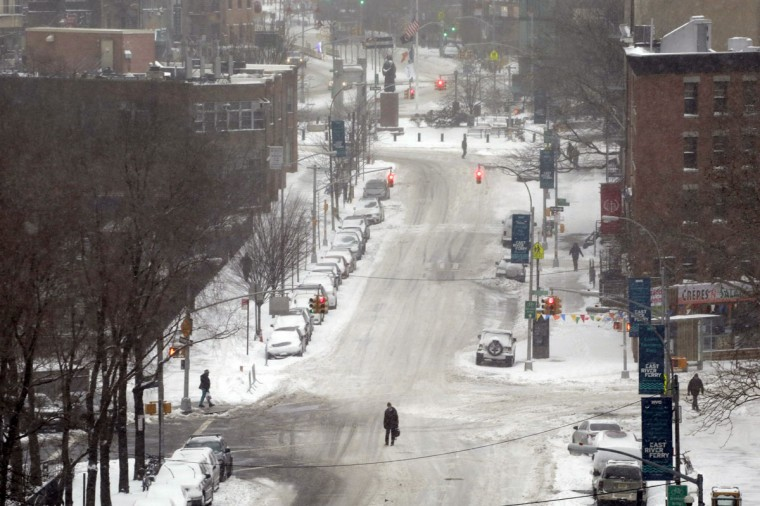 A pedestrian crosses an empty snow-covered street, Tuesday, Jan. 27, 2015 in New York during a city-wide ban on non-emergency vehicles. (AP Photo/Mark Lennihan)