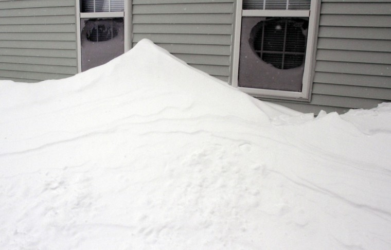Drifted snow is piled along the wall of a house after a winter storm, Tuesday, Jan. 27, 2015, in Marlborough, Mass. (AP Photo/Bill Sikes)