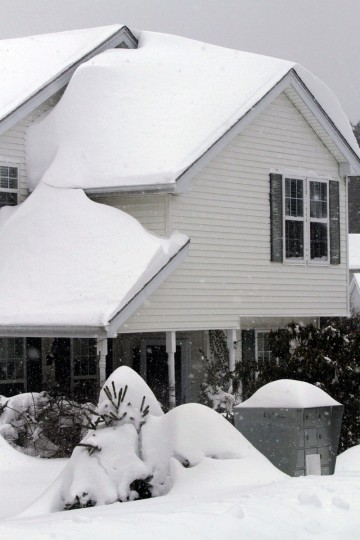 The roof of a house is covered in drifted snow after a winter storm, Tuesday, Jan. 27, 2015, in Marlborough, Mass. (AP Photo/Bill Sikes)