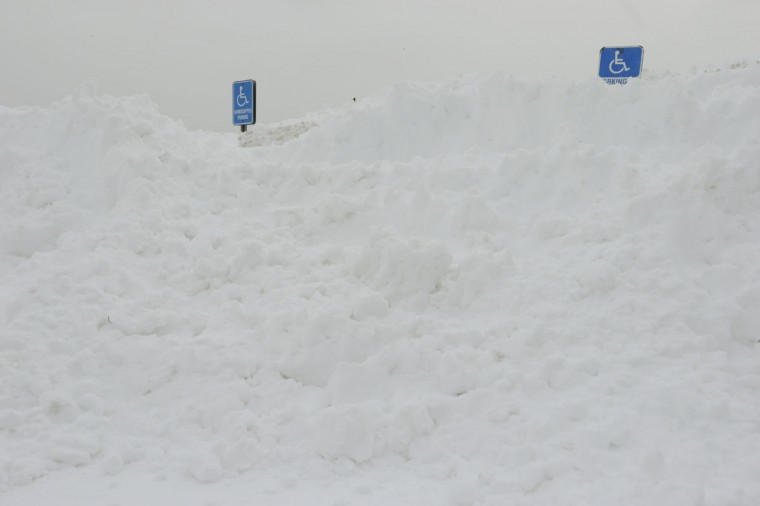 Handicap parking signs are buried in a snow mound, Tuesday, Jan. 27, 2015 in a Central Islip, N.Y shopping center parking lot. (AP Photo/Mary Altaffer)