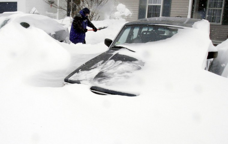 Paul Baxter digs his cars out of drifted snow after a winter storm, Tuesday, Jan. 27, 2015, in Marlborough, Mass. (AP Photo/Bill Sikes)