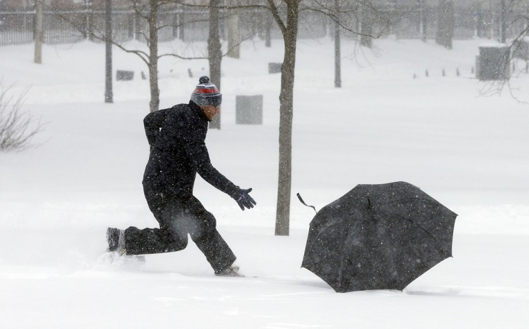 A man chases his umbrella during a winter snowstorm Tuesday, Jan. 27, 2015, in Boston. (AP Photo/Steven Senne)