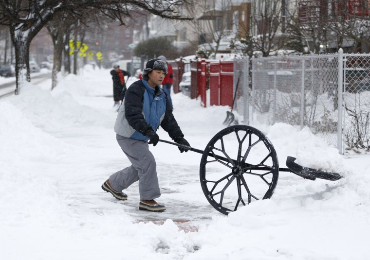 A man uses a shovel with a wheel to clean out a sidewalk following an overnight snowstorm, Tuesday, Jan. 27, 2015, in Jersey City, N.J. (AP Photo/Julio Cortez)