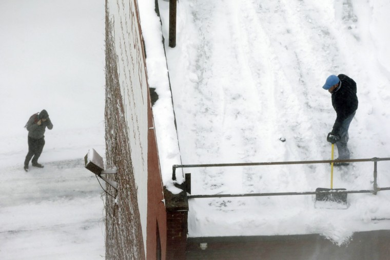 A worker clears snow from a rooftop, right, as a pedestrian passes below during a winter snowstorm Tuesday, Jan. 27, 2015, in Boston. (AP Photo/Steven Senne)