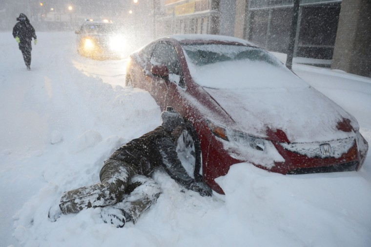 Tow truck driver Fawn Kleemann struggles to connect a tow cable to a car abandoned in Franklin Square in downtown Norwich, Conn., as police officer Elizabeth Harsley stands by, Tuesday, Jan. 27, 2015. (AP Photo/The Day, Sean D. Elliot)