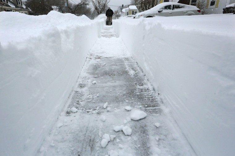Charlie Glover leaves a two foot tall path as he uses a snow blower to dig himself out of the snow on Tuesday, Jan. 27, 2015 in New Bedford, Mass. (AP Photo/Standard Times, Peter Pereira)