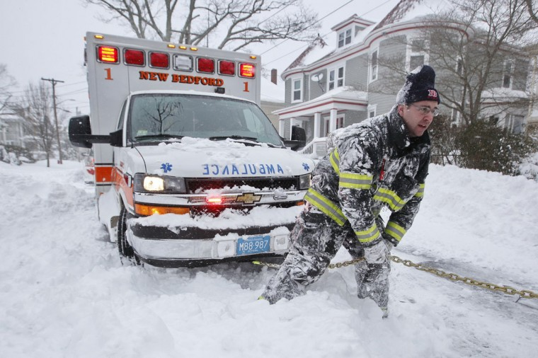 New Bedford firefighter Lt. Eric Hartford tries to dig out an ambulance carrying a patient en route to St. Lukes Hospital in New Bedford, Mass., on Tuesday, Jan. 27, 2015, as the region digs itself out of the snow storm that covered the area. (AP Photo/The Standard-Times, Peter Pereira)
