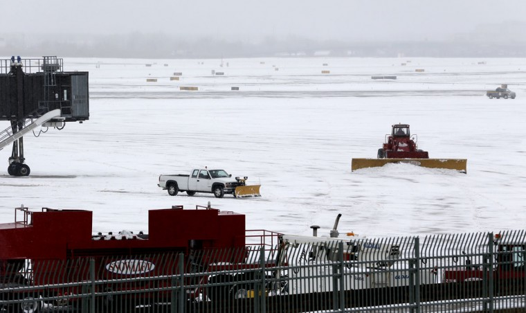 Trucks pushing plows clean up the tarmac area as United Airlines planes board at Newark Liberty International Airport following an overnight snowstorm, which forced the cancellation of most flights in and out of the airport, Tuesday, Jan. 27, 2015, in Newark, N.J. (AP Photo/Julio Cortez)