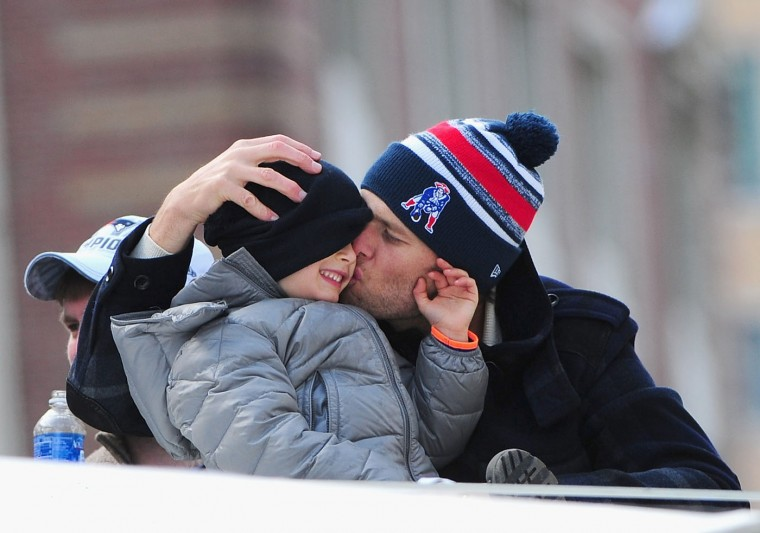 Quarterback Tom Brady of the New England Patriots kisses his son Benjamin during a Super Bowl victory parade on February 4, 2015 in Boston, Massachusetts. The Patriots defeated the Seattle Seahawks 28-24 in Super Bowl XLIX. (Photo by Billie Weiss/Getty Images)