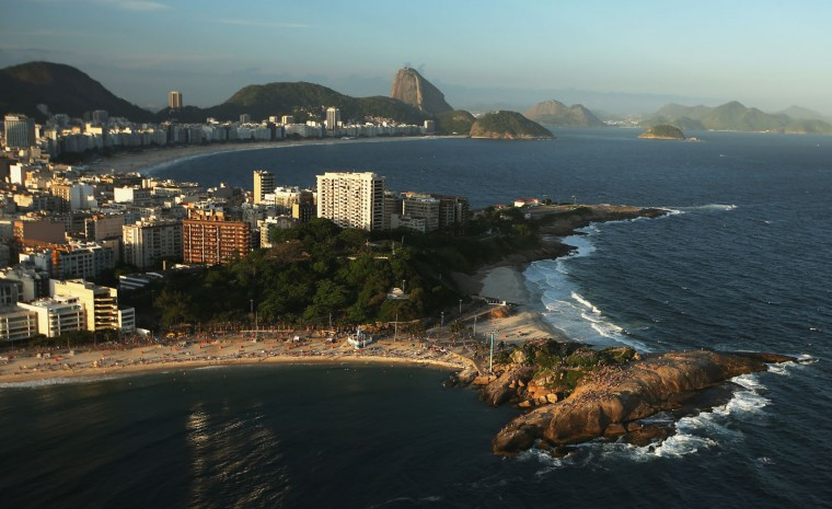 The sun begins to set over Copacabana beach (TOP), which will host beach volleyball, open water marathon and triathlon for the Rio 2016 Olympic Games, on February 24, 2015 in Rio de Janeiro, Brazil. The city of Rio continues to prepare to host the upcoming Olympic Games which kickoff on August 5, 2016. (Photo by Mario Tama/Getty Images)
