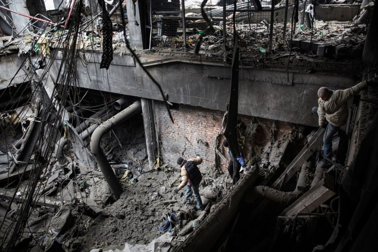 Ukrainian soldier prisoners-of-war are forced by pro-Russian rebels to search through the wreckage of the destroyed Donetsk airport for weaponry and dead bodies on February 26, 2015 in Donetsk, Ukraine. The Donetsk airport has been one of the most heavily fought over pieces of land between the Ukrainian army and pro-Russian rebels. (Photo by Andrew Burton/Getty Images)
