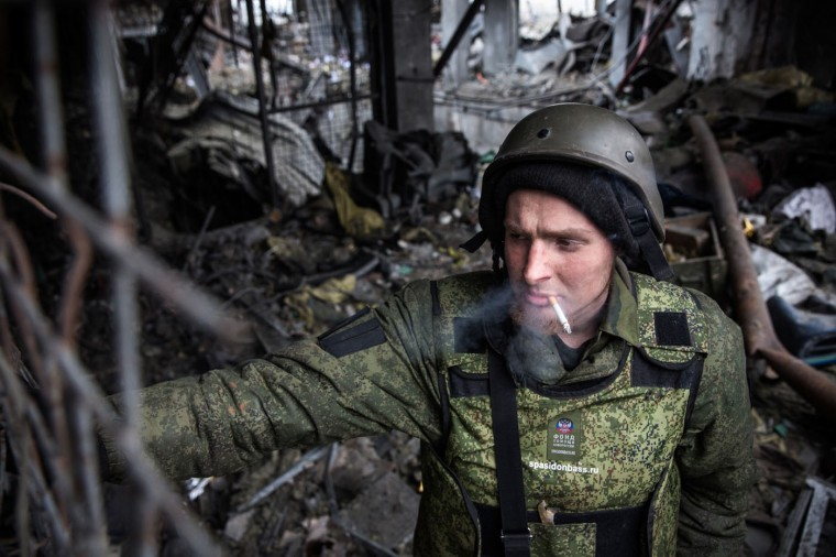 A pro-Russian rebel stands guard while Ukrainian soldier prisoners-of-war are forced to search through the wreckage of the destroyed Donetsk airport for weaponry and dead bodies on February 26, 2015 in Donetsk, Ukraine. The Donetsk airport has been one of the most heavily fought over pieces of land between the Ukrainian army and pro-Russian rebels. (Photo by Andrew Burton/Getty Images)