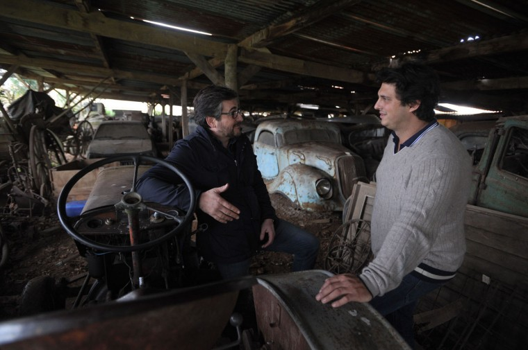"""Artcurial Motorcars managing director Matthieu Lamoure (L) and expert Pierre Novikov (R) speak on November 26, 2014 at the Gaillard property in the western French town of Echire among a collection of 60 antique cars, dating from the '30s to the '70s, including Bugatti, Hispano-Suiza, Delahaye, Maserati and Ferrari models, some of them rare, parked in makeshift shelters. The cars, called by experts """"an automotbile Graal,"""" were collected by Roger Baillon, who died in the early 2000s before being able to open a car museum as he had wanted to. The rare car collection was auctionned off on December 6 by Artcurial during the Retromobile fair in Paris. (Xavier Letoy/AFP/Getty Images)"""