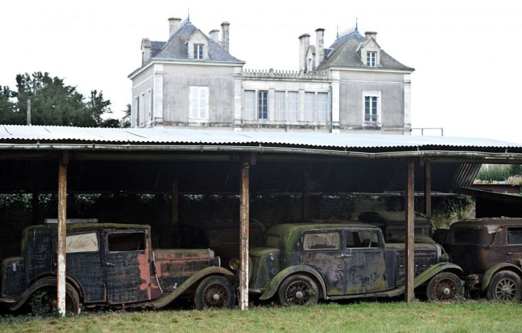 """A collection of 60 antique cars, dating from the '30s to the '70s, including Bugatti, Hispano-Suiza, Delahaye, Maserati and Ferrari models, some of them rare, are parked on November 26, 2014 in makeshift shelters at the Gaillard property in the western French town of Echire. The cars, called by experts """"an automotbile Graal,"""" were collected by Roger Baillon, who died in the early 2000s before being able to open a car museum as he had wanted to. The rare car collection, estimated at was auctionned off on December 6 by Artcurial during the Retromobile fair in Paris. (Xavier Letoy/AFP/Getty Images)"""