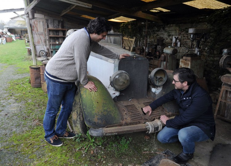 """Artcurial Motorcars managing director Matthieu Lamoure (R) and expert Pierre Novikov (L) check a model on November 26, 2014 at the Gaillard property in the western French town of Echire among a collection of 60 antique cars, dating from the '30s to the '70s, including Bugatti, Hispano-Suiza, Delahaye, Maserati and Ferrari models, some of them rare, parked in makeshift shelters. The cars, called by experts """"an automotbile Graal,"""" were collected by Roger Baillon, who died in the early 2000s before being able to open a car museum as he had wanted to. The rare car collection was auctionned off on December 6 by Artcurial during the Retromobile fair in Paris. (Xavier Letoy/AFP/Getty Images)"""