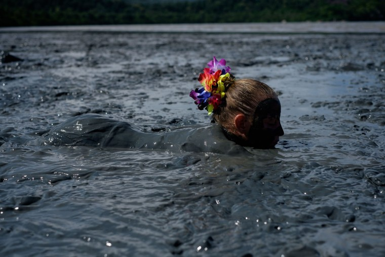 "A reveller prepares for ""Bloco da Lama,"" a mud carnival in Paraty, about 250km south of Rio de Janeiro, Brazil, on February 14, 2015. ""Bloco da Lama"" was started in 1986 by two teenagers playing with mud. Yasuyoshi Chiba/AFP/Getty Images"