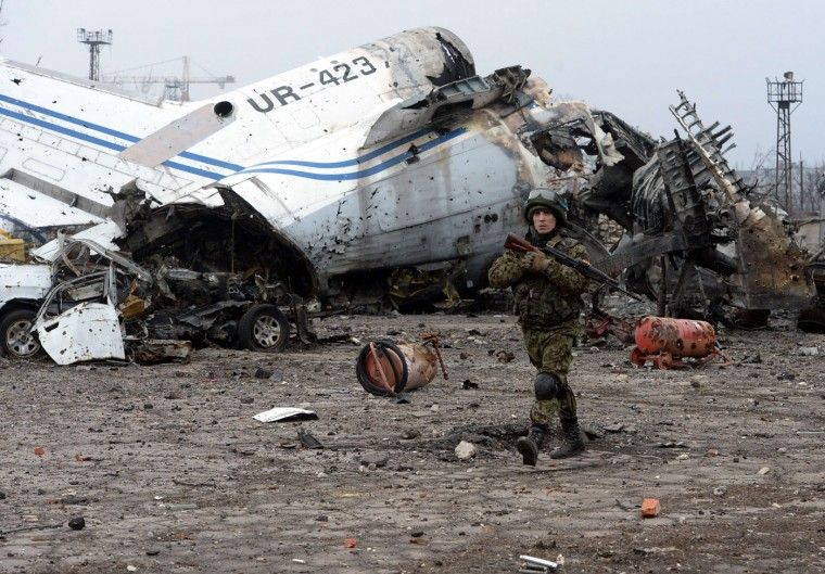 An armed fighter of self-proclamed People's Republic of Donetsk walks past a damaged airplane in the destroyed airport of the eastern Ukrainian city of Donetsk, on February 26, 2015. Ukraine's military said Thursday it was starting the withdrawal of heavy weapons from the frontline with pro-Russian rebels, a key step in a stuttering peace plan. The start of the withdrawal by Kiev comes after a shaky truce that was meant to come into force February 15 finally took hold across the Ukraine conflict zone in recent days. (Vasily Maximov/AFP/Getty Images)