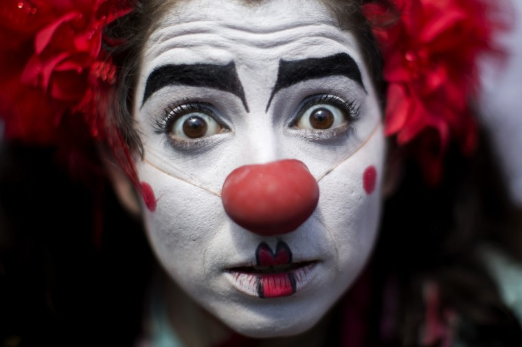 """A reveler dressed as a clown poses for a photo during the 'Gigantes da Lira' carnival parade in Rio de Janeiro, Brazil, Sunday, Feb. 8, 2015. Rio's over-the-top Carnival is the highlight of the year for many local residents. Hundreds of thousands of merrymakers are beginning to take to the streets in open-air """"blocos"""" parties. (AP Photo/Felipe Dana)"""