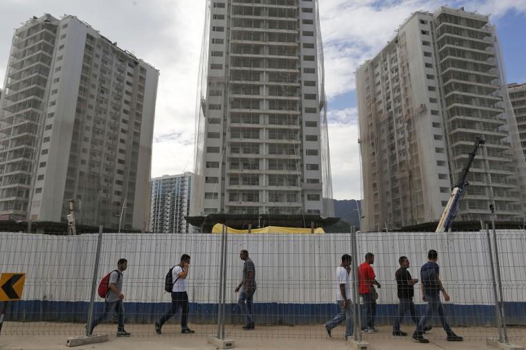 People walk past the 2016 Olympic Games's Athletes Village under construction in Rio de Janeiro, Brazil, Thursday, Feb. 19, 2015. . (AP Photo/Leo Correa)