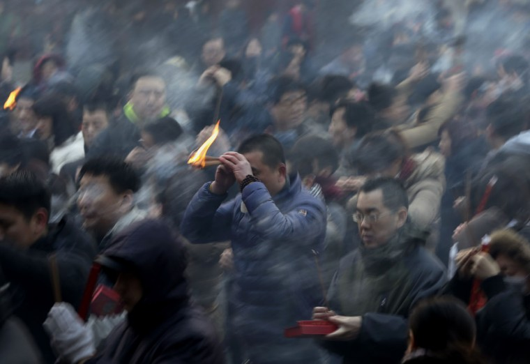 A man holds burning incense as he offers prayers on the first day of the Chinese Lunar New Year at Yonghegong Lama Temple in Beijing, China Thursday, Feb. 19, 2015. Chinese people are celebrating the arrival of the Lunar New Year, the Year of the Sheep. (Andy Wong/AP Photo)