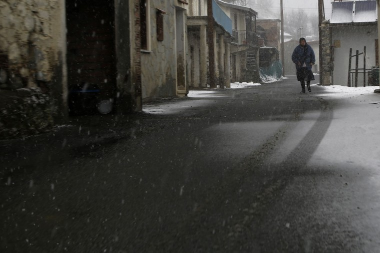 An elderly woman walks during a snowfall in Kiperounta village on Troodos mountains, Cyprus, Thursday, Feb. 19, 2015. The cold front brought unseasonably cold temperatures and plenty of snow on Cyprus' Troodos mountain range. Schools were closed in many small mountain villages and communities as a result of the snowfall that made roads treacherous. Even the capital Nicosia saw rare snow flurries. Temperatures are forecast to rise over the weekend. (Petros Karadjias/AP Photo)