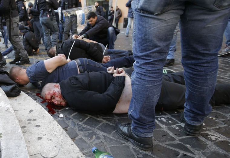 An injured Feyenoord's fan lies on the ground after being arrested with others during clashes occurred with Italian Policemen at the Spanish steps prior to the start of the Europa League soccer match between Roma and Feyenoord in Rome, Thursday, Feb. 19, 2015. (Gregorio Borgia/AP Photo)
