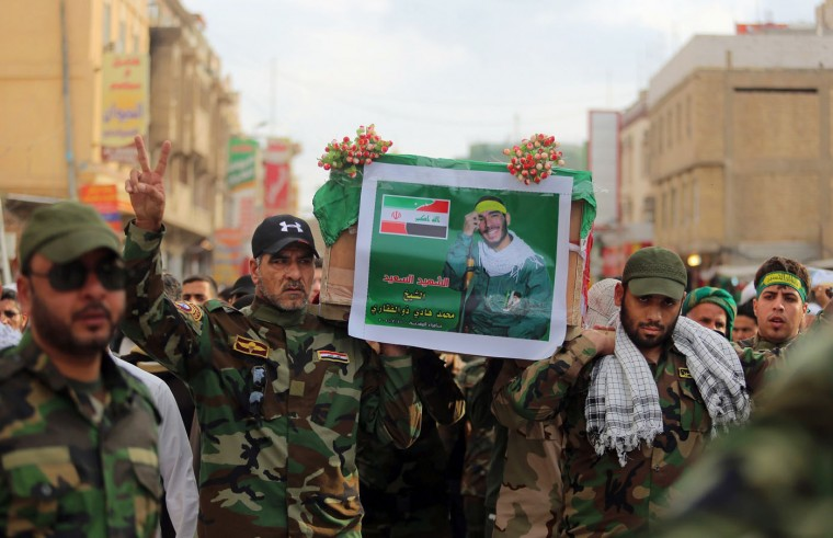 Iraqi and Iranian Shiite militiamen carry the coffin draped with Iranian flag during a funeral procession for Mohammad Hadi Zulfiqar, in the poster, an Iranian volunteer fighting in the Badr Brigades Shiite militia, in Najaf, 100 miles (160 kilometers) south of Baghdad, Iraq, Thursday, Feb. 19, 2015. Zulfiqar was killed during a battle against the Islamic State extremist group in Samarra, a town north of Baghdad that is home to a major Shiite shrine. (Jaber al-Helo/AP Photo)
