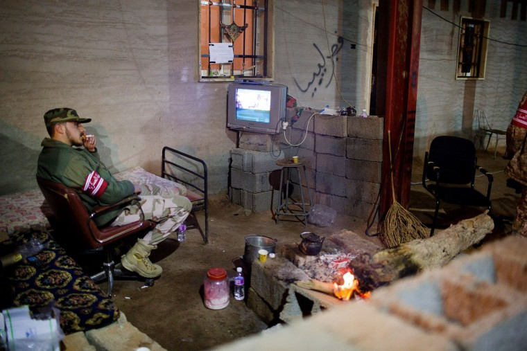 In this Wednesday, Feb. 18, 2015 photo, a Libyan military soldier smokes his cigarette as he watches the news during his break, 110 kilometers (68 miles) from Sirte, Libya. (Mohamed Ben Khalifa/AP Photo)