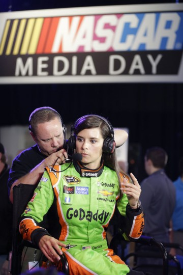 A technician adjusts the headset for driver Danica Patrick as she prepares for an interview during NASCAR media day at Daytona International Speedway, Thursday, Feb. 12, 2015, in Daytona Beach, Fla. (John Raoux/AP)