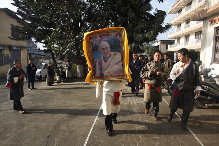 A Tibetan man carries a portrait of spiritual leader the Dalai Lama during Tibetan New Year, or Losar, inside the Tibetan Refugee Camp in Lalitpur, Nepal, Thursday, Feb. 19, 2015. Tibetans across the world marked the arrival of the New Year with prayers and festivities. (Niranjan Shrestha/AP Photo)