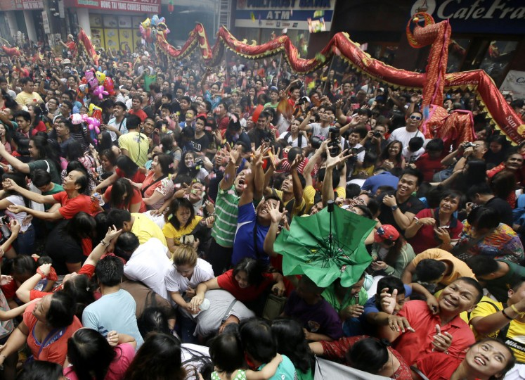 "Crowd catch sweets and giveaways being thrown at them following dragon and lion dances performed in front of a supermarket at Manila's Chinatown district of Binondo to celebrate the Chinese New Year Thursday, Feb. 19, 2015, Philippines. This year marks the ""Year of the Sheep"" in the Chinese Lunar calendar. (Bullit Marquez/AP Photo)"