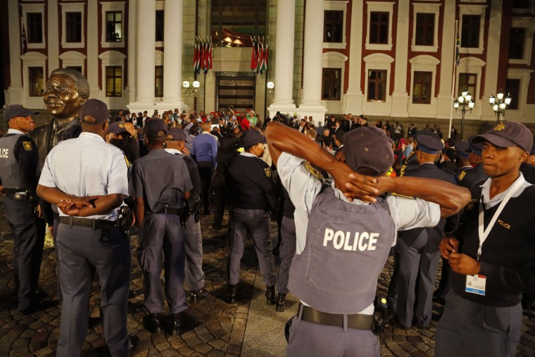 South African Police provide security at the entrance to Parliament after the session was disrupted during the official opening session in Cape Town, South Africa, Thursday, Feb. 12, 2015. Security guards entered South Africa's parliament on Thursday to remove opposition lawmakers who disrupted an annual address by President Jacob Zuma to demand that he answer questions about a spending scandal. (Schalk van Zuydam/Pool/AP)