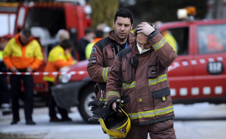 Firemen work in the area of a chemical explosion in Igualada, Spain, Thursday, Feb. 12, 2015. Spanish authorities Thursday ordered the residents of five northeastern towns to stay indoors for some two hours after a chemical explosion at a warehouse spread a large, orange toxic cloud over the area. A spokeswoman for Catalonia's regional firefighting department said the blast occurred when products being delivered to a warehouse in the city of Igualada became mixed, exploded and set a truck on fire. She said two people were slightly injured. Firefighters said the chemicals were nitric acid and ferric chloride. The region's Civil Protection department ordered some 65,000 residents of Igualada and four nearby towns to stay indoors until the cloud dissipated. The order was lifted two hours later but maintained for pregnant women, children, elderly people and those with respiratory problems. (Manu Fernandez/AP)