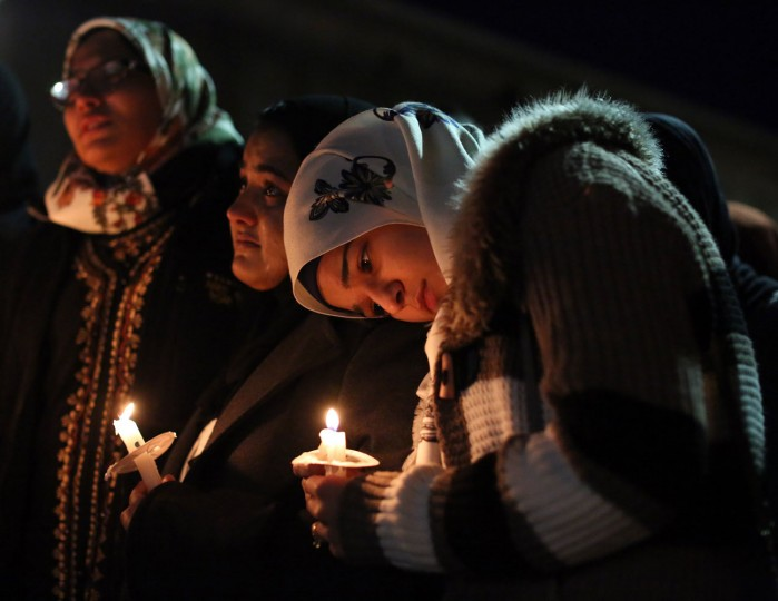 Suzanne Askar, right, rests her head on the shoulder of Safam Mahate, a student at North Carolina State University, as they stand next to Nida Allam, far left, during a vigil for three people who were killed at a condominium near UNC-Chapel Hill, Wednesday, Feb. 11, 2015, in Chapel Hill, N.C. Craig Stephen Hicks appeared in court on charges of first-degree murder in the Tuesday deaths of Deah Shaddy Barakat, his wife Yusor Mohammad and her sister Razan Mohammad Abu-Salha. (Al Drago/News & Observer/AP)