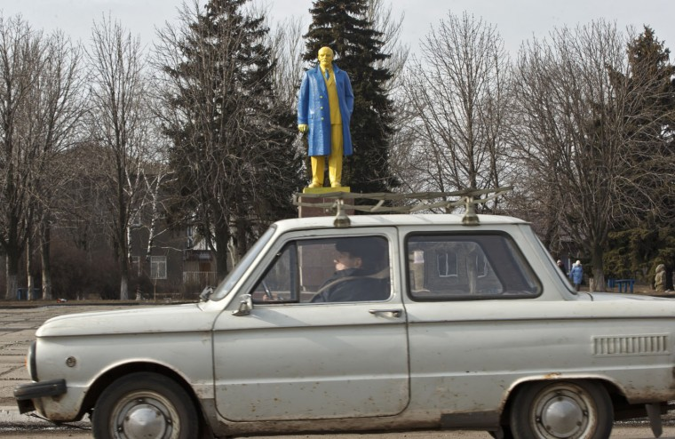 A man rides in a car by a statue of Lenin, painted in the colors of Ukraine's national flag, in Velyka Novosilka, Ukraine, Thursday, Feb. 19, 2015, near the border between Russia backed rebels and Ukrainian held territories, on the Ukrainian side. A Ukrainian military spokesman says more than 90 percent of its forces have been withdrawn from the fiercely contested town of Debaltseve and its surroundings, but left unclear when the retreat might be completed. (Vadim Ghirda/AP Photo)