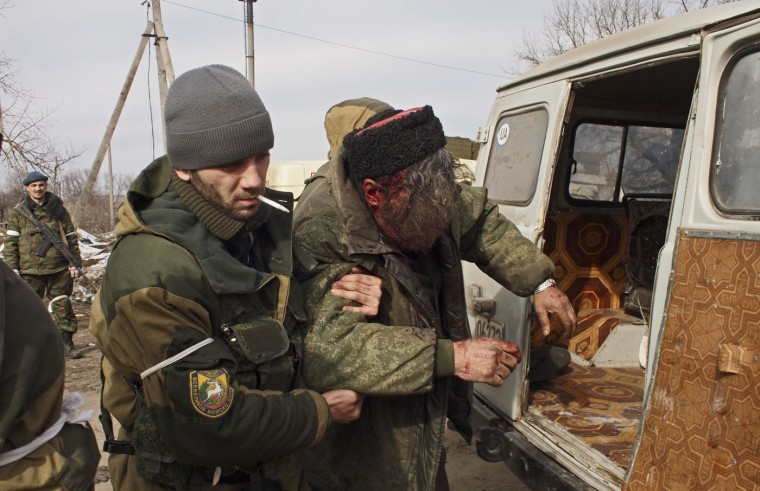 A wounded Cossack is carried away by fellow fighters after his car hit a land mine in the east Ukraine town of Debaltseve on Thursday, Feb. 19, 2015. After weeks of relentless fighting, the embattled Ukrainian rail hub of Debaltseve fell Wednesday to Russia-backed separatists, who hoisted a flag in triumph over the town. The Ukrainian president confirmed that he had ordered troops to pull out and the rebels reported taking hundreds of soldiers captive. (Peter Leonard/AP Photo)