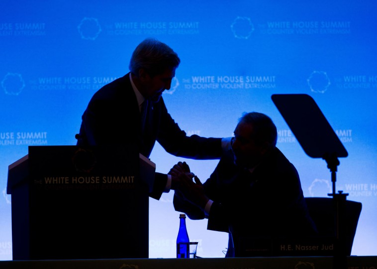 Secretary of State John Kerry, left, greets Jordan's Foreign Affairs Minister Nasser Judeh, right, as they are silhouetted on stage at the opening of the Countering Violent Extremism (CVE) Summit, Thursday, Feb. 19, 2015, at the State Department in Washington. The White House is conveying a three-day summit to bring together local, federal, and international leaders to discuss steps the US and its partners can take to develop community-oriented approaches to counter extremist ideologies that radicalize, recruit and incite to violence. (Pablo Martinez Monsivais/AP Photo)