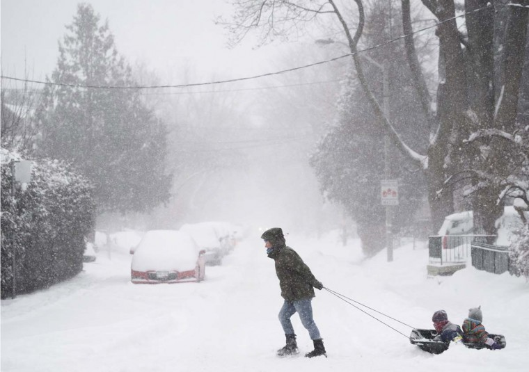 A woman pulls children in a sled during a storm with strong winds and heavy snow, Monday, Feb. 2, 2015, in Toronto. (AP Photo/The Canadian Press, Darren Calabrese)
