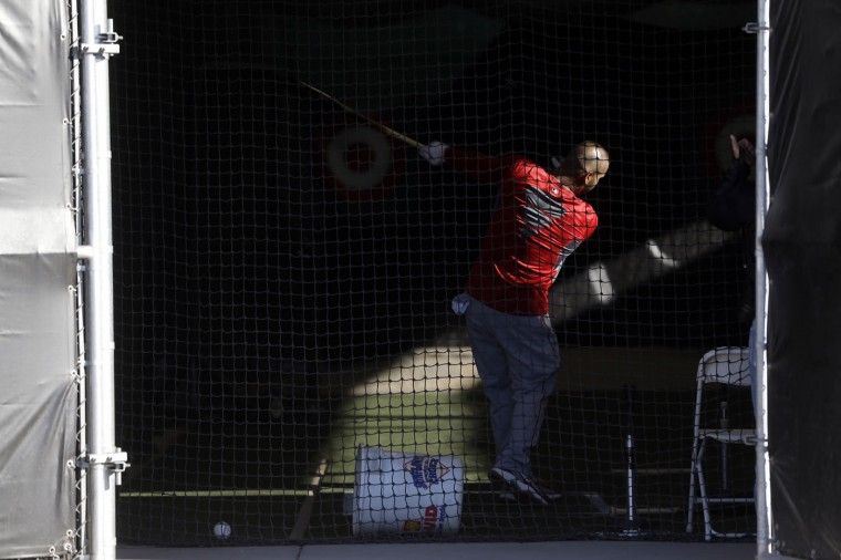 Los Angeles Angels' Albert Pujols hits balls in a batting cage before a spring training baseball workout Wednesday, Feb. 25, 2015, in Tempe, Ariz. (AP Photo/Morry Gash)