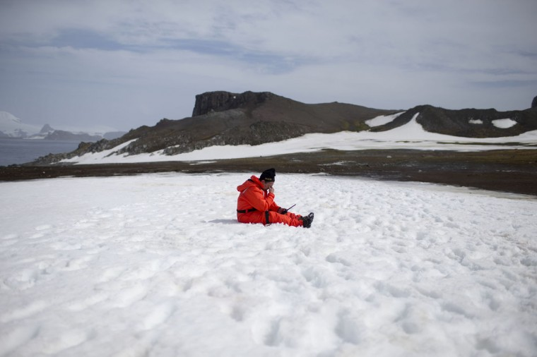 In this Jan. 24, 2015 photo, a worker from the Chile's Antarctic Institute sits on the snow on Robert Island, part of the South Shetland Islands archipelago in Antarctica. NASA uses the remoteness of Antarctic to study what people would have to go through if they visited Mars. The dry air also makes it perfect for astronomers to peer deep into space and into the past. (AP Photo/Natacha Pisarenko)