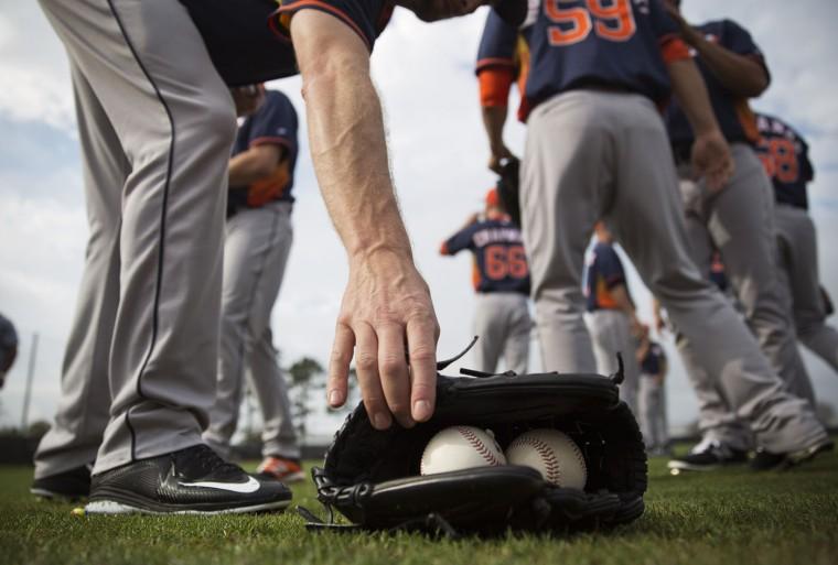 Houston Astros pitcher Scott Feldman reaches for his glove during a spring training baseball workout, Tuesday, Feb. 24, 2015, in Kissimmee, Fla. (AP Photo/David Goldman)