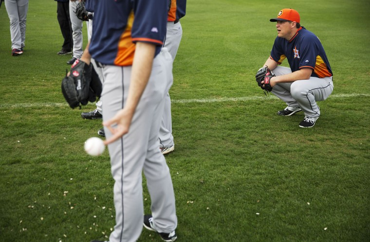 Houston Astros pitcher Will Harris, right, listens to instructions to fellow pitchers during a spring training baseball workout, Tuesday, Feb. 24, 2015, in Kissimmee, Fla. (AP Photo/David Goldman)