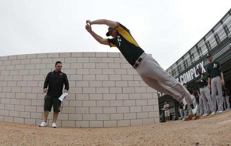 Oakland Athletics' Taylor Thompson jumps during spring training baseball practice Friday, Feb. 20, 2015, in Mesa, Ariz. (AP Photo/Darron Cummings)