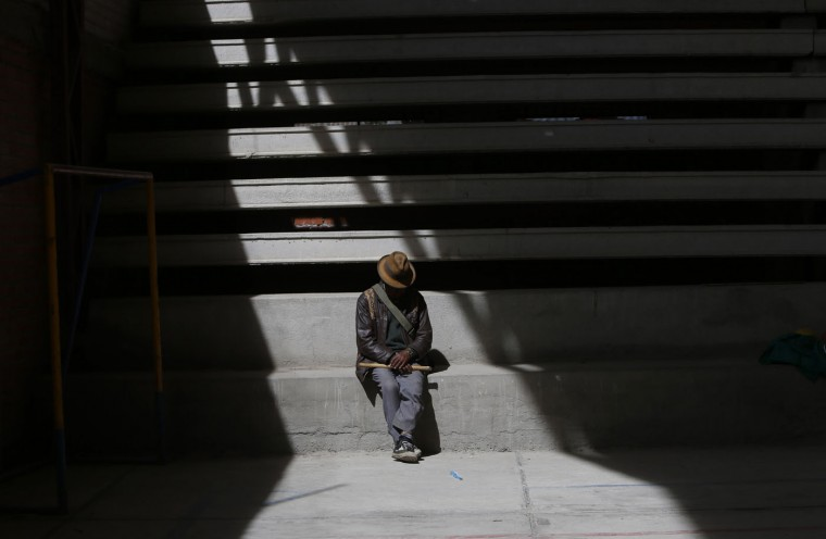 In this Feb. 4, 2105 photo, an Aymara man holding a flute rests in the stands of covered court in El Alto, Bolivia. The man watched elderly Aymara indigenous women play handball. (AP Photo/Juan Karita)