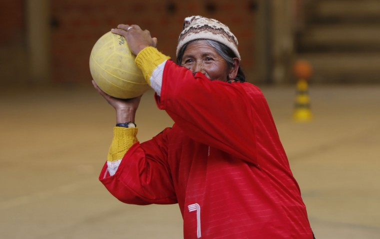 In this Feb. 4, 2105 photo, 72-year-old Aurea Murillo prepares to make a pass during a handball match among elderly Aymara indigenous women in El Alto, Bolivia. Murillo said now that her children are grown she's dedicating time to herself and that playing handball makes her feel good. (AP Photo/Juan Karita)